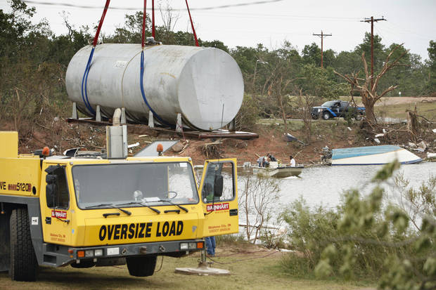 A gasoline tank that was blown from it's concrete enclosure into Lake Thunderbird is removed on Wednesday, May 12, 2010, in Norman, Okla.   The tank at the Marina on East Alameda landed upright and did not spill its contents into the lake.  Photo by Steve Sisney, The Oklahoman