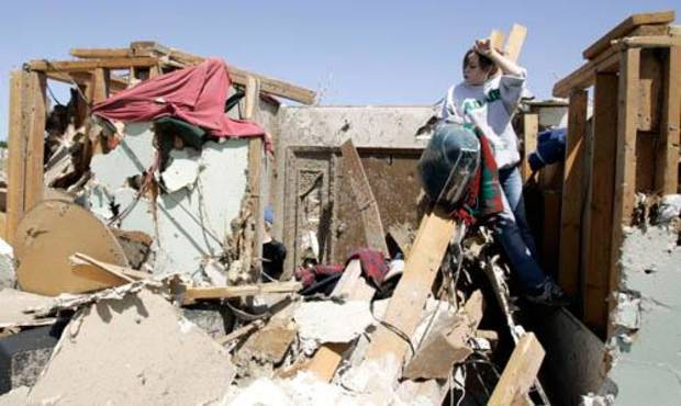 Mackenzie Stogsdill takes a break while sifting through the remains of a damaged house after a Saturday tornado hit Picher, Okla., Sunday, May 11, 2008. BY MATT STRASEN, THE OKLAHOMAN