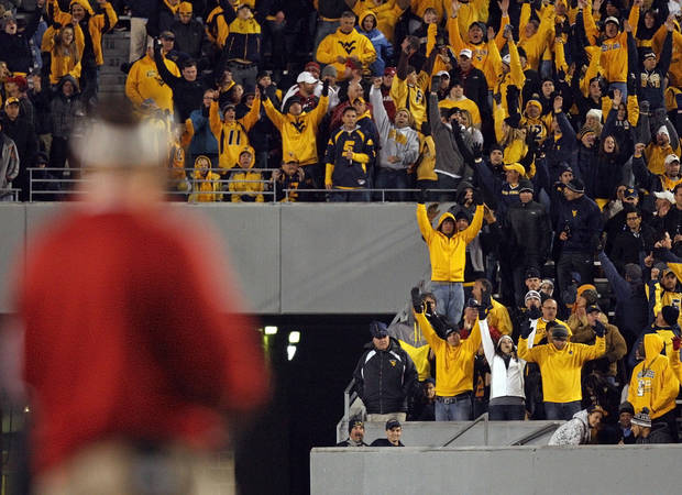West Virginia fans react after a Mountaineer touchdown was confirmed by replay as OU head coach Bob Stoops stands on the sideline during a college football game between the University of Oklahoma and West Virginia University on Mountaineer Field at Milan Puskar Stadium in Morgantown, W. Va., Nov. 17, 2012. OU won, 50-49. Photo by Nate Billings, The Oklahoman