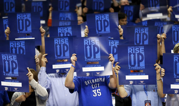 Fans hold signs honoring members of the military during Military Appreciation Night during an NBA basketball game between the Oklahoma City Thunder and the Washington Wizards at Chesapeake Energy Arena on Wednesday, March 27, 2013. Photo by Nate Billings/The Oklahoman