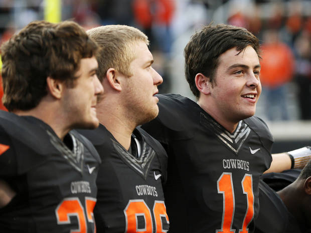 Oklahoma State's Wes Lunt (11), right, sings the alma mater along with Alex Elkins (37), left, and Zac Veatch (86) after a college football game between Oklahoma State University (OSU) and Texas Christian University (TCU) at Boone Pickens Stadium in Stillwater, Okla., Saturday, Oct. 27, 2012. OSU won, 36-14. Photo by Nate Billings, The Oklahoman