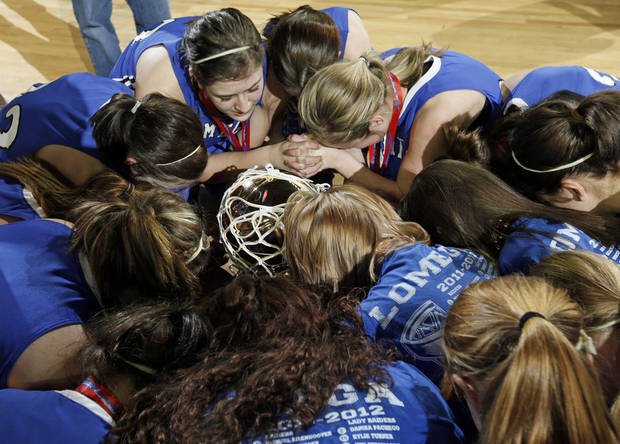 The Lomega Raiderettes kneel around the gold ball championship trophy to pray after the Class B girls state championship high school basketball game between Hammon and Lomega at State Fair Arena in Oklahoma City, Saturday, March 3, 2012. Lomega won, 49-44. Photo by Nate Billings, The Oklahoman
