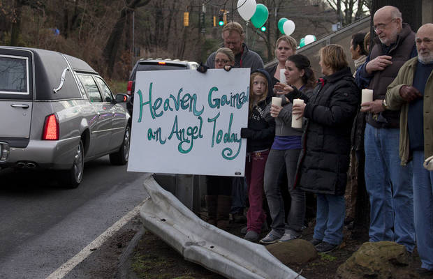 Friends and co-workers hold a sign as the hearse and funeral procession for James Mattioli, 6, who died in the Sandy Hook Elementary School shootings, approaches the St. John's Cemetery Tuesday, Dec. 18, 2012, in Darien, Conn. Adam Lanza walked into Sandy Hook Elementary School in Newtown Dec. 14,  and opened fire, killing 26 people, including 20 children. Tuesday, Dec. 18, 2012. (AP Photo/Craig Ruttle) ORG XMIT: CTCR105