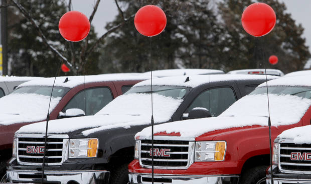 Balloons fly over snow covered pickup trucks on Broadway in Oklahoma City, Wednesday February  20, 2013. Photo By Steve Gooch, The Oklahoman