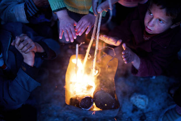 Syrian children warm themselves at a refugee camp near the Turkish border, in Azaz, Syria, Sunday, Dec. 9, 2012. Temperatures dropped to 9 degrees Celsius (48 degrees Fahrenheit) in Azaz. (AP Photo/Manu Brabo)