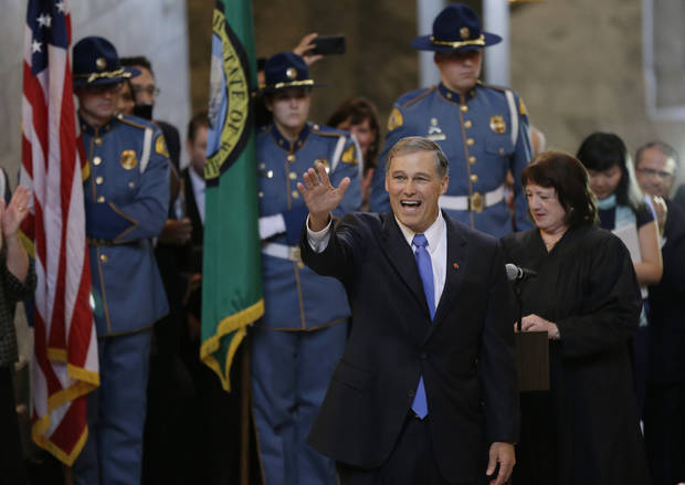 Jay Inslee, left, waves after being sworn in as Washington state Governor, Wednesday, Jan. 16, 2013, by Washington Supreme Court Chief Justice Barbara Madsen,right, in the rotunda of the Legislative Building at the Capitol in Olympia, Wash. (AP Photo/Ted S. Warren)