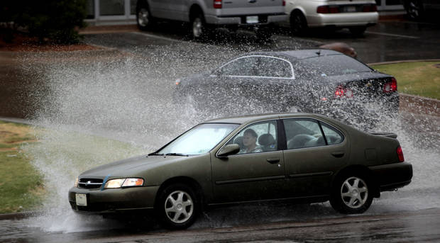 A car drives through a large puddle on Penn Ave. near Memorial Road during a rain shower in Oklahoma City, Saturday, Aug. 18, 2012. Photo by Sarah Phipps, The Oklahoman