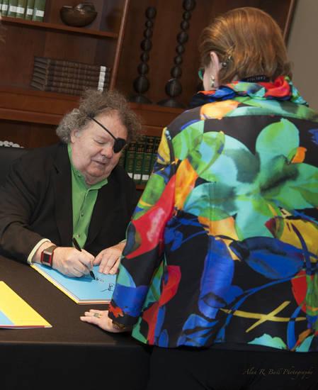 Famed glass artist Dale Chihuly signs a copy of one of his books for a fan during his June 24 visit to the Oklahoma City Museum of Art. Chihuly gave an invitation-only lecture at the museum, followed by a book signing for museum members. Photo provided by the Oklahoma City Museum of Art. <strong></strong>