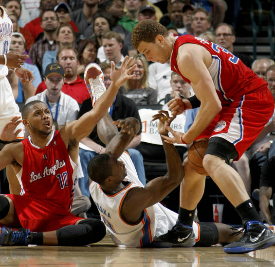 Oklahoma City's Serge Ibaka (9) fights for the ball with Los Angeles Clippers' Eric Gordon (10) and Blake Griffin (32) during the NBA basketball game between the Oklahoma City Thunder and the Los Angeles at the Oklahoma City Arena, Wednesday, April 6, 2011. Photo by Bryan Terry, The Oklahoman