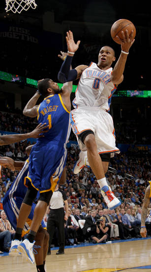 Oklahoma City's Russell Westbrook (0) leaps past Golden State's Dorell Wright (1) to the basket during the NBA basketball game between the Oklahoma City Thunder and the Golden State Warriors at the Oklahoma City Arena, Tuesday, March 29, 2011. Photo by Bryan Terry, The Oklahoman