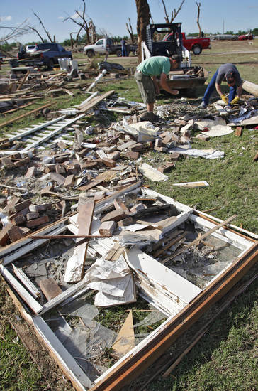 J.T. Chronister, left, and Joe Jainese dig through rubble from a home destroyed by Tuesday's tornado north of El Reno, Wednesday, May 25, 2011. Photo by Chris Landsberger, The Oklahoman
