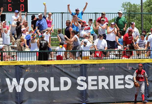 A fan catches a home run ball as Alabama's Jennifer Fenton (7) walks away during the Women's College World Series game between Florida and Alabama at the ASA Hall of Fame Stadium in Oklahoma City, Sunday, June 5, 2011. Photo by Garett Fisbeck, The Oklahoman