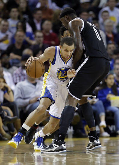 Golden State Warriors' Stephen Curry, left, tries to dribble around Brooklyn Nets' Andray Blatche (0) during the first half of an NBA basketball game in Oakland, Calif., Wednesday, Nov. 21, 2012. (AP Photo/Marcio Jose Sanchez)