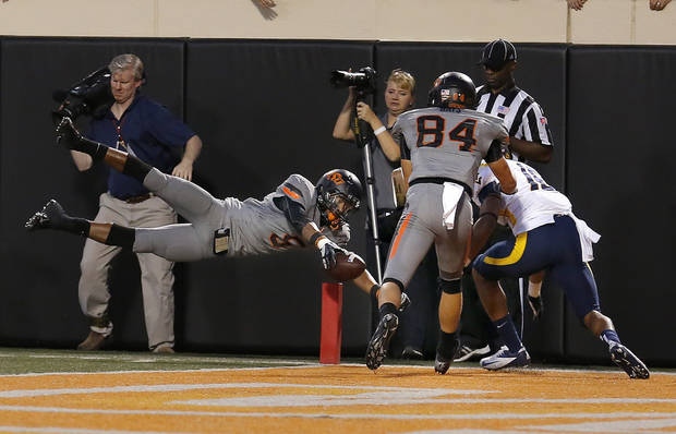 Oklahoma State&#039;s Josh Stewart (5) dives for a touchdown in the fourth quarter during a college football game between Oklahoma State University (OSU) and the West Virginia University at Boone Pickens Stadium in Stillwater, Okla., Saturday, Nov. 10, 2012. Photo by Sarah Phipps, The Oklahoman
