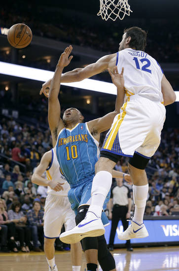 Golden State Warriors center Andrew Bogut (12), from Australia, blocks a shot by New Orleans Hornets guard Eric Gordon (10) during the first quarter of an NBA basketball game in Oakland, Calif., Wednesday, April 3, 2013. (AP Photo/Jeff Chiu)