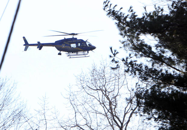 A Connecticut State Police helicopter hovers over the scene near the Sandy Hook School following a shooting , Friday, Dec. 14, 2012 in Newtown, Conn.(AP Photo/The Journal News, Frank Becerra Jr.) MANDATORY CREDIT, NYC OUT, NO SALES, TV OUT, NEWSDAY OUT; MAGS OUT ORG XMIT: NYWHI129