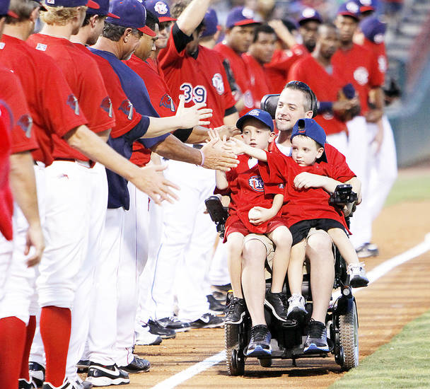 Oklahoma City police officer Chad Peery, with sons McKade and Morgan, is honored Aug. 27 at an Oklahoma City RedHawks game. Photo by Nate Billings, The Oklahoman