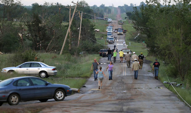 Residents walk down a street in Carney, Okla., after a tornado swept through the area on Sunday, May 19, 2013. Photo by Bryan Terry, The Oklahoman