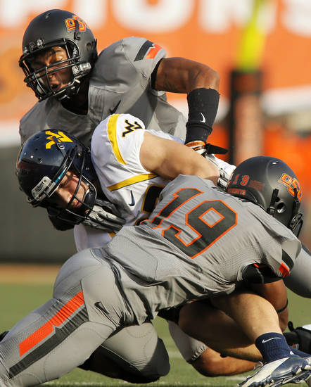 Oklahoma State's Lyndell Johnson (27), back, and Brodrick Brown (19) stop West Virginia's Connor Arlia (83) during a college football game between Oklahoma State University (OSU) and West Virginia University (WVU) at Boone Pickens Stadium in Stillwater, Okla., Saturday, Nov. 10, 2012. Photo by Nate Billings, The Oklahoman