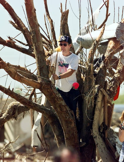 Tornado damage: A spectator climbs a tree in hopes of getting a better view of  President Bill Clinton in Del City.
