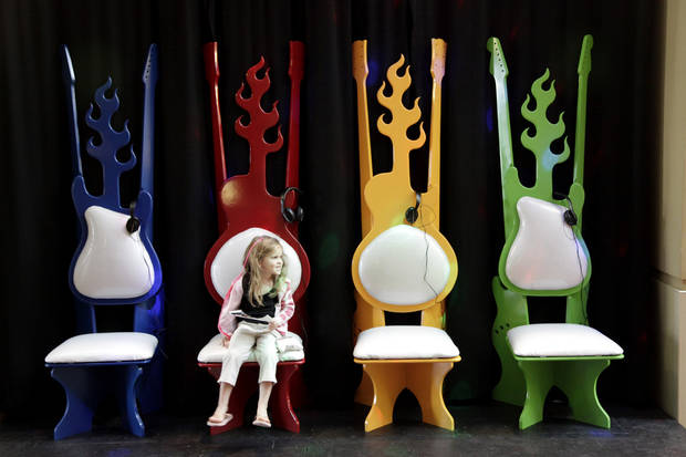 "Marina Glapion, 5, from Midwest City, sits in colorful guitar chairs at the opening of ""Another Hot Oklahoma Night"" rock 'n' roll history exhibit at the Oklahoma History Center Saturday, May 2, 2009. Photo by Doug Hoke, The Oklahoman"