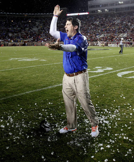 "Florida head coach Will Muschamp does the ""Gator Chomp"" in celebration after being doused following a victory over Florida State in an NCAA college football game on Saturday, Nov. 24, 2012, in Tallahassee, Fla. Florida defeated Florida State 37-26. (AP Photo/The Gainesville Sun, Matt Stamey)"