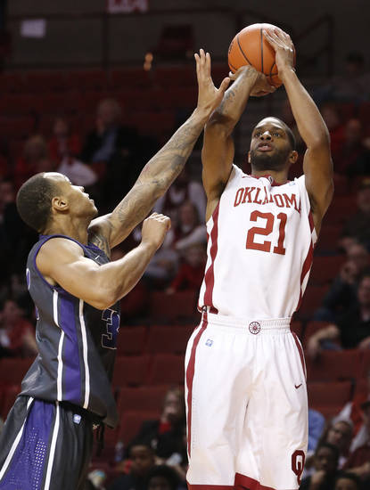 Oklahoma guard Cameron Clark (21) shoots in front of TCU guard Garlon Green (33) in the second half of an NCAA college basketball game in Norman, Okla., Monday, Feb. 11, 2013. Oklahoma won 75-48. (AP Photo/Sue Ogrocki)