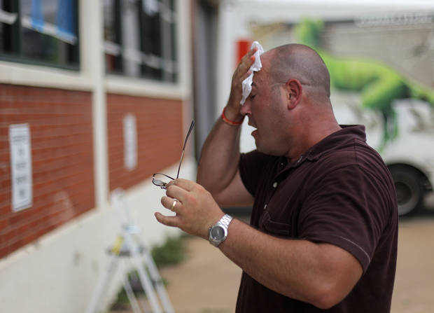 OKLAHOMA CITY THUNDER / NBA FINALS / NBA BASKETBALL / SUPPORT / MIAMI HEAT:  Daniel Cochran, an employee at The Brace Place, takes a break from painting windows outside of his office building to wipe sweat from his face in Oklahoma City, Monday, June 11, 2012.  Photo by Garett Fisbeck, The Oklahoman