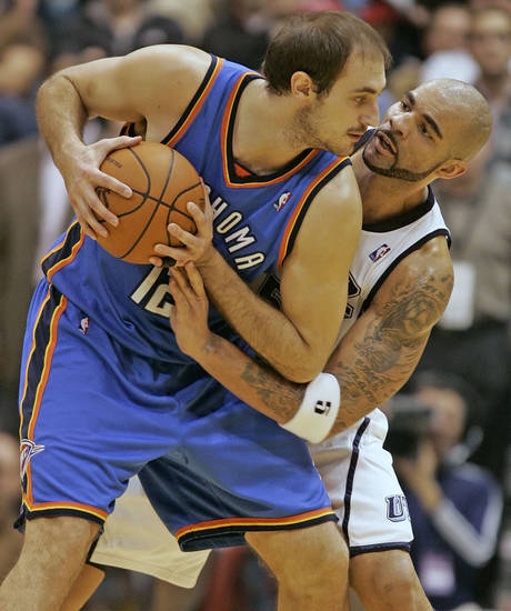 Utah Jazz's Carlos Boozer, right, reaches in on Oklahoma City Thunder's Nenad Krstic during the second half of an NBA basketball game in Salt Lake City, Saturday, Nov. 24, 2009. The Thunder beat the Jazz 104-94. (AP Photo/George Frey)