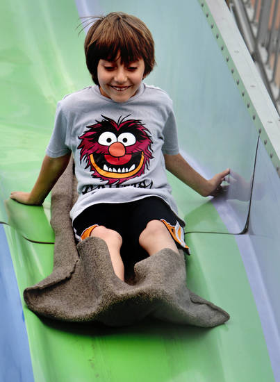 August Bibbs-Nauni, 7, from Midwest City, slides down a giant slide at the Lions Carnival on Saturday, April 28, 2012, in Norman, Okla.  Photo by Steve Sisney, The Oklahoman