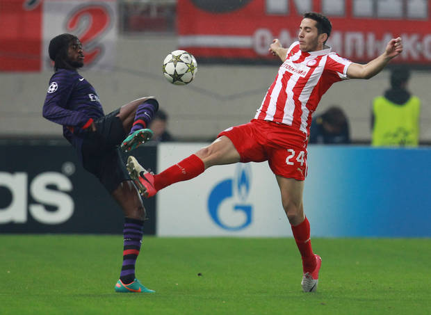 Olympiakos' Kostas Manolas, right, fights for the ball with Arsenal's Gervinho during their group B Champions League soccer match in the port of Piraeus, near Athens, Tuesday, Dec. 4, 2012. (AP Photo/Thanassis Stavrakis)