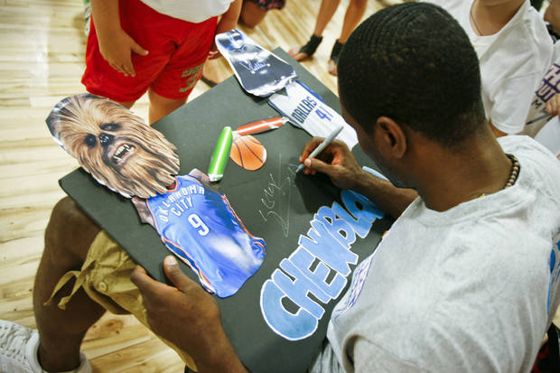 Serge Ibaka autographs a sign made by 9-year-old Colby Robinson of Edmond at the Thunder Youth Basketball Camp at the Santa Fe Family Life Center on Tuesday, June 14, 2011. Photo by Zach Gray, The Oklahoman 