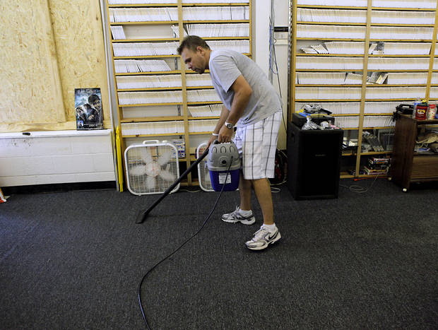 Michael Bartmann, co owner of 2001 Video and BBC Home Furniture, vacuums water and broken glass at his shop in Perry, Okla., on Tuesday, Aug. 9, 2011. Severe storms on Monday night damaged buildings in Perry. Photo by John Clanton, The Oklahoman