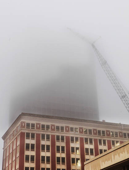 A construction crane and the Sandridge tower disappear into the fog above the Braniff Building in downtown Oklahoma City Wednesday, Feb. 15, 2012. Photo by Paul B. Southerland, The Oklahoman