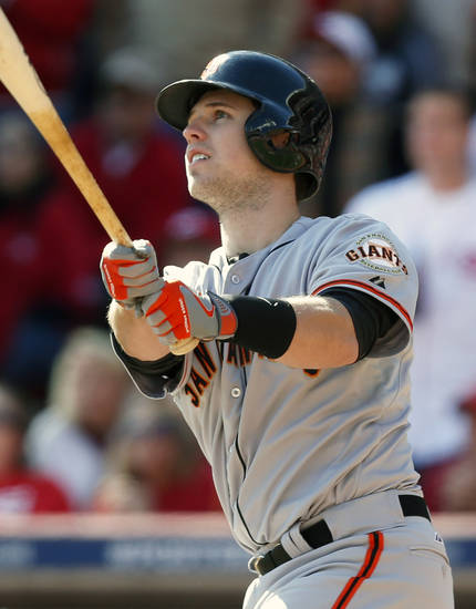 San Francisco Giants' Buster Posey hits a grand slam off Cincinnati Reds starting pitcher Mat Latos in the fifth inning of Game 5 of the National League division baseball series, Thursday, Oct. 11, 2012, in Cincinnati. (AP Photo/David Kohl)
