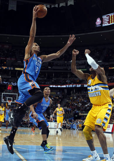 Oklahoma City Thunder guard Thabo Sefolosha, left, of Switzerland, goes up for a shot over Denver Nuggets guard Andre Iguodala in the first quarter of an NBA basketball game in Denver on Sunday, Jan. 20, 2013. (AP Photo/David Zalubowski)