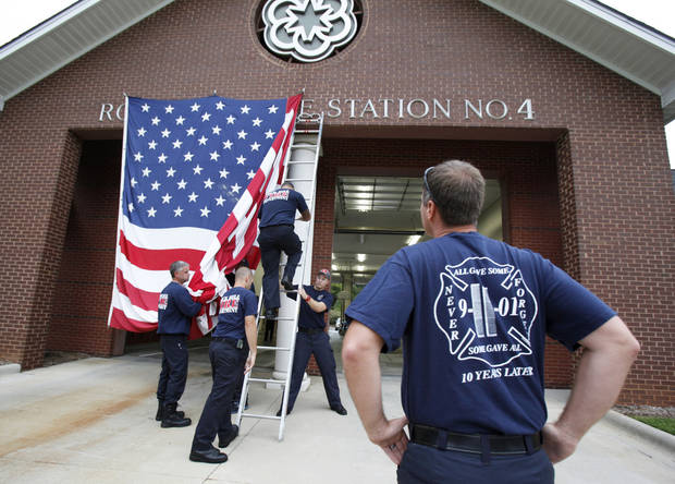 Capt. Kris Small of the Rock Hill, S.C. Fire Department watches as other Rock Hill firefighters put a giant American Flag on the front of Station 4 on Tuesday, Sept. 11. 2012 to commemorate Sept. 11 terrorist attacks. (AP Photo/ The Herald, Andy B urriss)