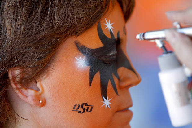 Joel Atkins of Stillwater gets his face painted before the OSU-Arizona game Thursday night in Stillwater. PHOTO BY BRYAN TERRY, The Oklahoman