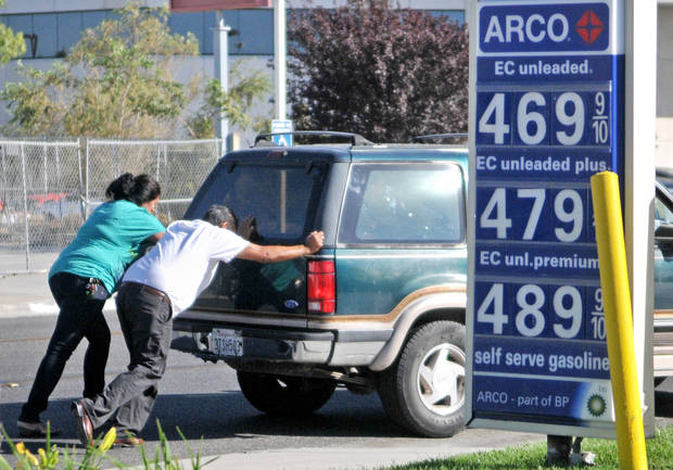 A man and a women help push Regina Chavira's SUV into a Arco gas station after Chavira ran out of gas less than 100 yards away as she was on her way to the gas station in Victorville, Calif, on Monday, Oct. 8, 2012. (AP Photo/The Victor Valley Daily Press, David Pardo)