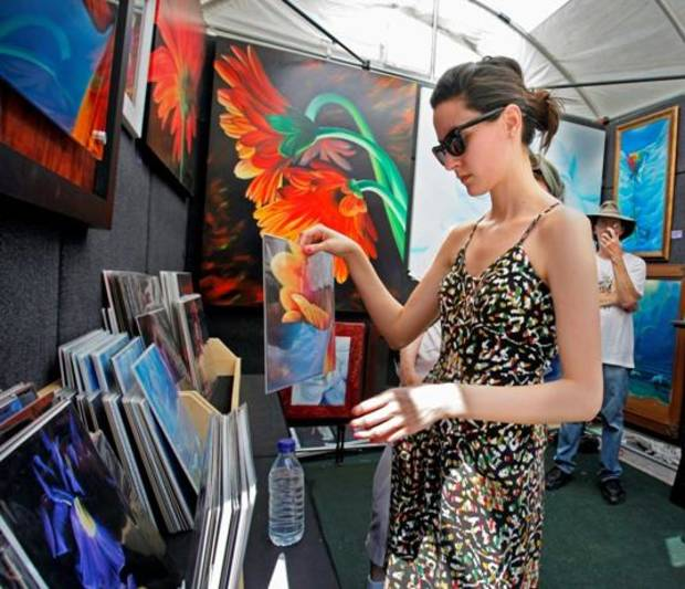 Kathryn Hernandez, Bethany, looks at the art of Stephen Hackley, Dallas, Texas (right) during the Paseo Arts Festival on Saturday, May 28, 2011, in Oklahoma City, Okla.   Photo by Steve Sisney, The Oklahoman