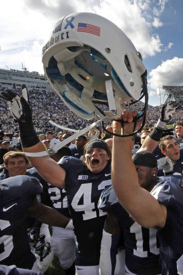 In this image taken with a fisheye lens, Penn State linebacker Michael Mauti, center, celebrates with teammates after they beat Northwestern 39-28 in an NCAA college football game, Saturday, Oct. 6, 2012, in State College, Pa. (AP Photo/Gene J. Puskar)
