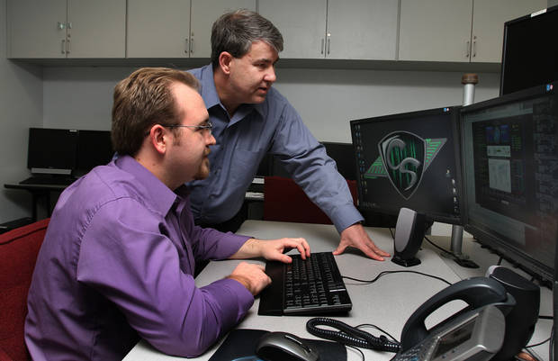Professor of Computer Information Technology Ken Dewey explains cyber security software to student Caleb Glave at Rose State College in Midwest City, Wednesday, January 11, 2012. PHOTO BY HUGH SCOTT, FOR THE OKLAHOMAN  ORG XMIT: KOD