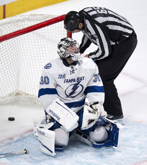 The linesman retrieves the puck in the net behind Tampa Bay Lightning goalie Ben Bishop following a power-play goal by Montreal Canadiens' Brian Gionta during the third period of their NHL hockey game, Thursday, April 18, 2013, in Montreal. The Canadiens won 3-2. (AP Photo/The Canadian Press, Paul Chiasson)