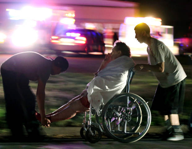 An injured elderly person is assisted Wednesday by two young males as a nursing home is evacuated after an explosion at a nearby fertilizer plant in West, Texas.  AP Photo