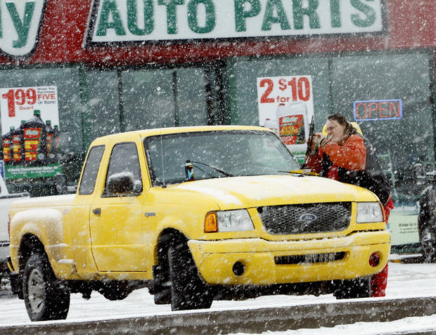 A motorist puts new wiper blades on her pickup on Friday, Jan. 29, 2010, in Purcell, Okla.  A winter storm knocked power out to much of the town Thursday and Friday.  Photo by Steve Sisney, The Oklahoman