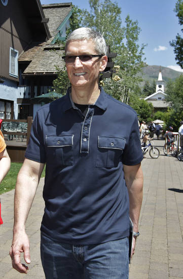 In his Thursday, July 12, 2012 photo, Apple CEO Tim Cook walks to the Allen & Company Sun Valley Conference in Sun Valley, Idaho. Apple Inc. reports quarterly financial results after the market closes on Tuesday, July 24. (AP Photo/Paul Sakuma)