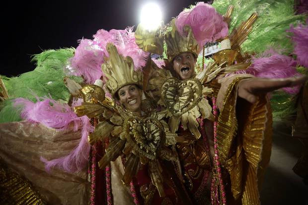 "U.S. citizen Paul Leaury, right, and an unidentified fellow foreign member of the Mangueira samba school, dance during a carnival parade at the Sambadrome in Rio de Janeiro, Brazil, Tuesday, Feb. 12, 2013. While non-Brazilians have long shelled out hundreds of dollars for the right to dress up in over-the-top costumes and boogie in Rio's samba school parades, which wrapped up Monday in an all-night extravaganza, few in the so-called ""alas dos gringos,"" or �foreigners' wings,� know how to dance the samba well, bopping along goofily in the parades and waving at the crowds of spectators. (AP Photo/Silvia Izquierdo)"