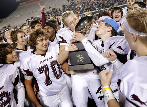 Blanchard's Zach Hill, center, kisses the championship trophy after winning the Class 3A football championship between Blanchard and Kingfisher at Boone Pickens Stadium in Stillwater, Okla., Friday, Dec. 7, 2012. Blanchard won 28-21. Photo by Bryan Terry, The Oklahoman