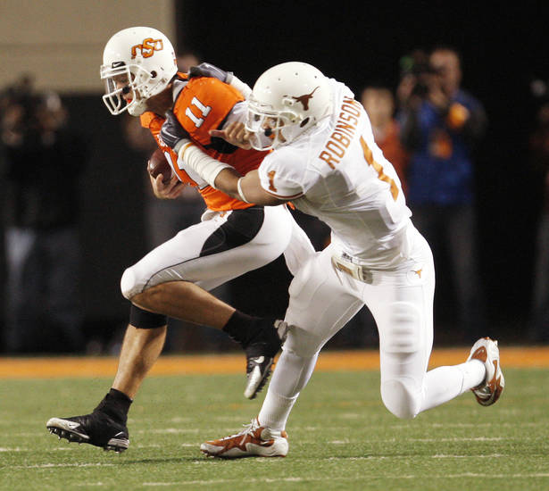 OSU quarterback Zac Robinson, left, is collared by Texas&amp;#8217; Keenan Robinson during Saturday&amp;#8217;s game. Photo by DOUG HOKE, The Oklahoman