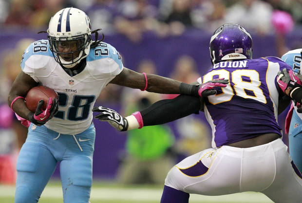 Tennessee Titans running back Chris Johnson, left, tries to break a tackle by Minnesota Vikings defensive tackle Letroy Guion during the first half of an NFL football game on Sunday, Oct. 7, 2012, in Minneapolis. (AP Photo/Genevieve Ross)